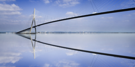 pillar of the bridge Pont du Normandie reflected in the Seine river at Le Havre, France