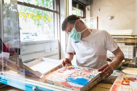 Photo pour Man is working in a pizza restaurant drive with his mask and covid 19 protection. Pandemic situation - image libre de droit