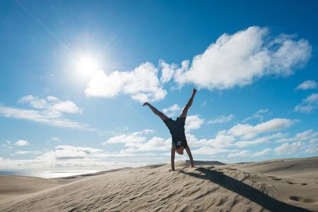 Young woman handstanding on the sand dunes of Te Paki, New Zealand