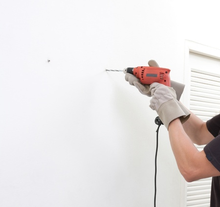 a man using an electric screwdriver with empty space on the wall