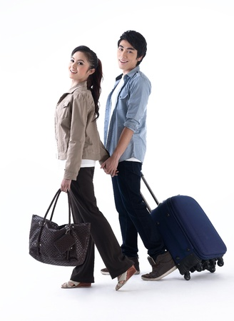 Young couple walking and pulling a luggage