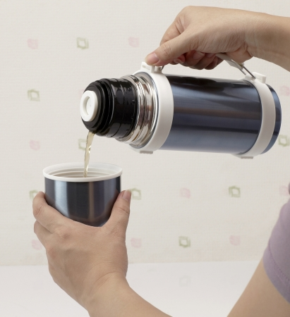 Pouring hot tea from thermos into cup