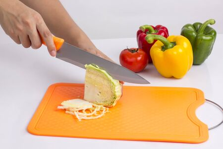 Foto de housewife cutting cabbage with knife on plastic cutting board on white background - Imagen libre de derechos