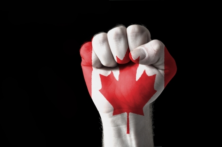 Low key picture of a fist painted in colors of canada flag