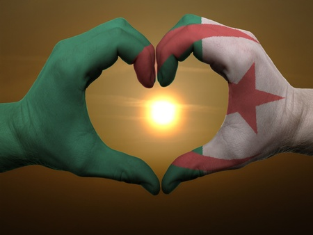 Gesture made by algeria flag colored hands showing symbol of heart and love during sunrise