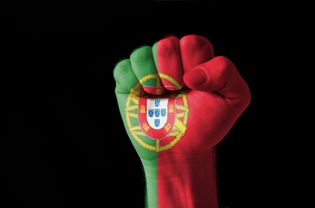Low key picture of a fist painted in colors of portugal flag