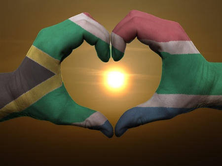 Gesture made by south africa flag colored hands showing symbol of heart and love during sunrise