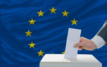 man putting ballot in a box during elections in european union