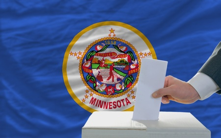 man putting ballot in a box during elections  in front of flag american state of minnesota