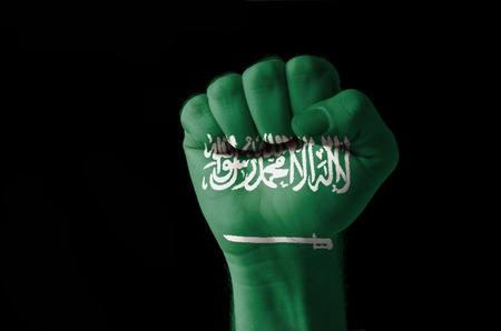 Low key picture of a fist painted in colors of saudi arabia flag