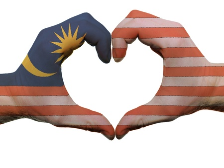Gesture made by malaysia flag colored hands showing symbol of heart and love, isolated on white background