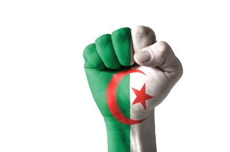 Low key picture of a fist painted in colors of algeria flag