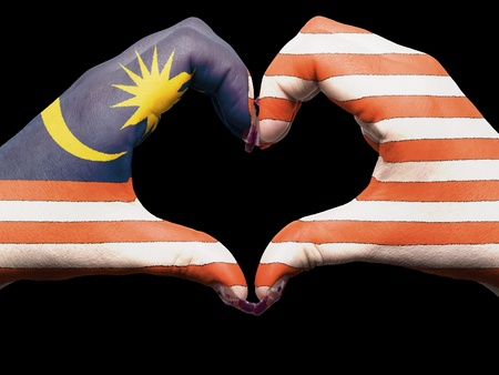 Tourist made gesture  by malaysia flag colored hands showing symbol of heart and love