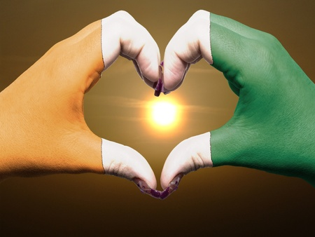 Tourist made gesture  by cote d'ivore flag colored hands showing symbol of heart and love during sunrise