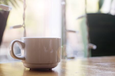 Photo pour White cup of coffee on a wooden table on a window background - image libre de droit