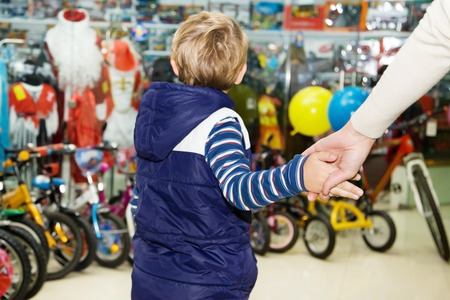 Mom firmly holding the baby by the hand in a toy store