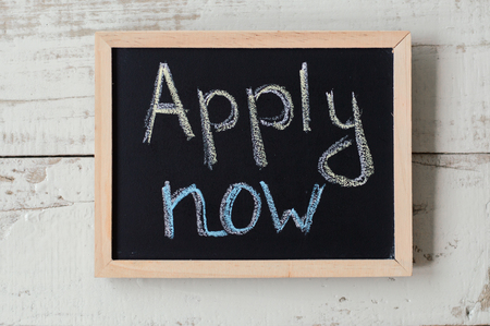 Apply now concept. Balckboard with handwritten text on wooden background. Employment and application process