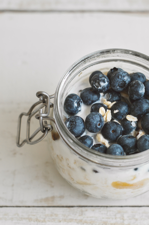 Overnight oats with coconut milk and fresh bluberry in a jur on wooden table, vertical photo. Easy breakfast recipe