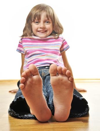 little girl sitting on a wooden floor