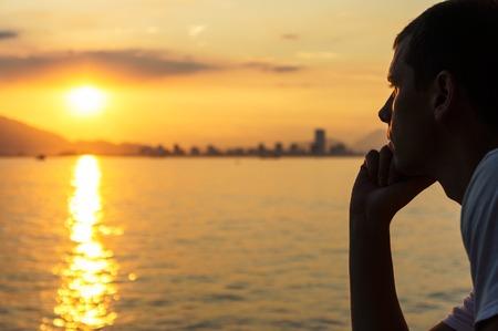 Photo pour Young man is looking at the sunrise. - image libre de droit