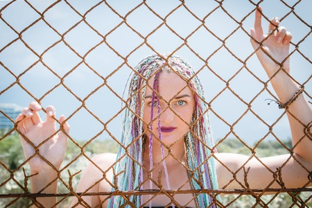 Foto per sexy girl in a swimsuit with pigtails with sunglasses standing near a metal grate fence, portrait, bit her lip. - Immagine Royalty Free