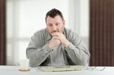 Sad middle-aged man is sitting at white desk. The bearded man wears a grey shirt. There are white cup, keyboard, glasses and window unfocused background
