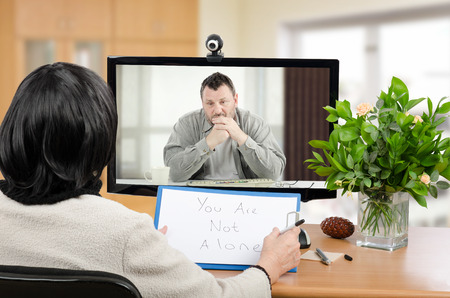 Photo for Middle aged man talks with psychotherapist via online video chat. He looking depressed. Black-haired woman holds written message for him - You are not alone. - Royalty Free Image
