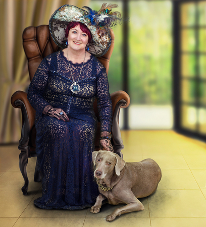 Full-height portrait of senior lady with weimaraner dog. Cheerful woman sits in wooden armchair. The dog lies next on yellow floor. Owner wears a dark guipure dress and big tapestry hat with feathers. Vertical shot on blurred interior background