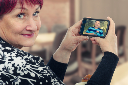 Old woman is happy on her first online date. She holding mobile phone. On the screen there is cheerful man with a rose. Concept of online dating for senior people