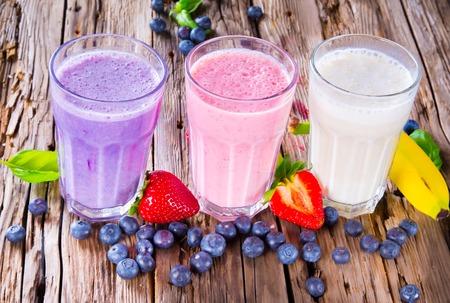 Foto für Fresh milk, strawberry, blueberry and banana drinks on wodeen table, assorted protein cocktails with fruits  - Lizenzfreies Bild