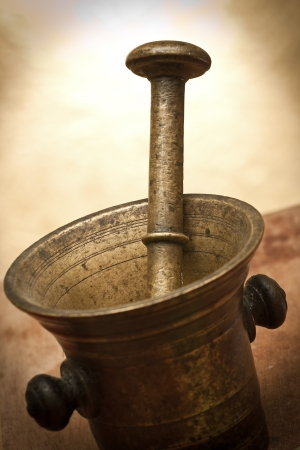 Photo pour Old bronze mortar and pestle with bay leaves on yellow background - image libre de droit