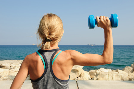 Photo pour Young athletic woman exercising outdoors: overhead press for upper body strength - image libre de droit