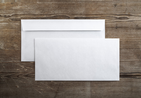 Photo of blank envelopes on a dark wooden background. Back and front. Template for branding identity. Top view.