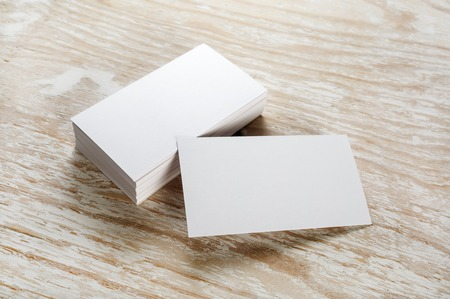 Photo of blank business cards with soft shadows on light wooden background. For design presentations and portfolios.