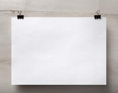 Blank white paper poster hanging on light wooden background. For design presentations and portfolios. Front view.