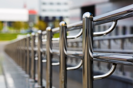 Foto per Chromium metal fence with handrail. Chrome-plated metal railings. Shallow depth of field. Selective focus. - Immagine Royalty Free