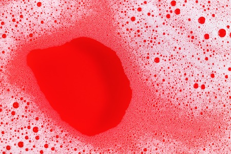 Foam with bubbles on red background. Shampoo or detergent in water. Flat lay.