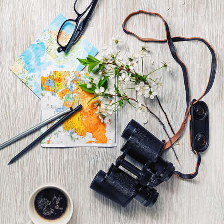 Photo for Planning vacation trip with map, binoculars, glasses, pencils, coffee cup and flowers. Travel or vacation concept. Flat lay. - Royalty Free Image