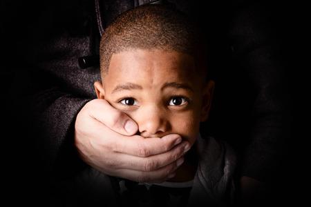 child being abducted over dark background