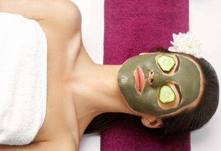 Spa Clay Mask. Woman with clay facial mask and cucumbers on eyes in beauty spa. Skincare. Beauty Concept. Close-up portrait of beautiful girl applying facial mask.Facial treatment. Cosmetology. Body care girl