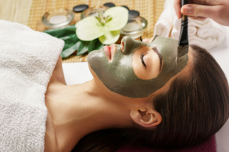 Face peeling mask, spa beauty treatment, skincare. Woman getting facial care by beautician at spa salon, side view, close-up.Spa clay mask on femele face.