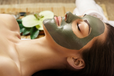 Spa Clay Mask. Woman with clay facial mask in beauty spa. Skincare. Beauty Concept. Close-up portrait of beautiful girl with facial mask.Facial treatment. Cosmetology. Body care girl