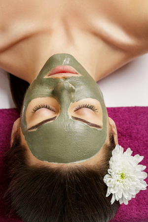 Spa Clay Mask. Woman with clay facial mask and cucumbers on eyes in beauty spa. Skincare. Beauty Concept. Close-up portrait of beautiful girl with facial mask.Facial treatment. Cosmetology. Body care girl