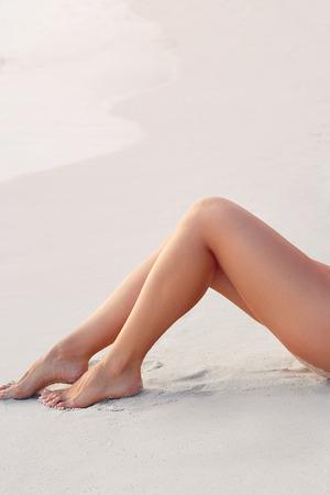 Photo pour Sexy Suntan Bikin Woman Legs Relaxing Lying Down near Beach.  Beauty Skincare. Protection Sun. Epilation Laser or Shaving Concept.Sunscreen on Feet - image libre de droit