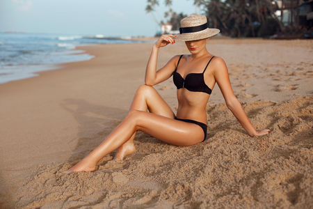 Photo pour Beautiful Sexy Woman with perfect body in bikini lying on beach. Skin care. Smooth tanned legs on the beach. Portrait of female in hat.Sunblock concept. Suntan - image libre de droit