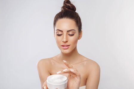 Photo pour Beauty Woman Face Skin Care. Portrait Of Attractive Young Female Applying Cream And Holding Bottle. Closeup Of Smiling Girl With Natural Makeup And Fresh Skin. Cosmetics. - image libre de droit