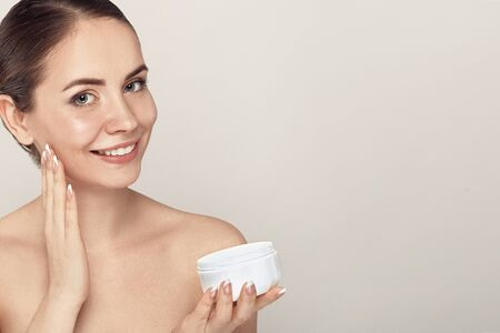 Photo pour Beauty Face of Woman Concept. Skin care. Portrait of female model  holding and applying cosmetic moisturizing cream and touch own face. Skin Protection. Cosmetology. Spa - image libre de droit