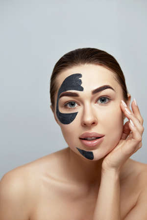 Photo pour Facial Mask. Beautiful Young Woman with black mask of clay on face .Skin care .Girl model with cosmetic mask. Facial treatment. Moisturizer Spa mask - image libre de droit