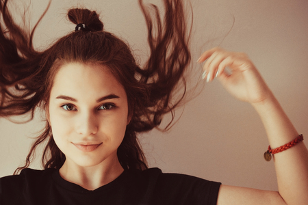 The face of a young girl, a teenager, on a light background. Hair flutter, look straight, smile. Youth, enthusiasm, fun. The hand is lifted up, in motion.