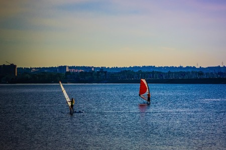 Two windsurfers on the water in the city. Summer, early evening. A modern sport. There are trees and an urban landscape in the distance.